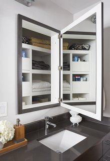 Photo caption: This renovation preserved the depth behind the medicine cabinets for linen storage.