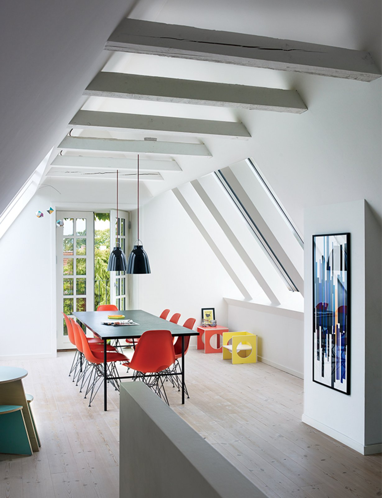Charrier transformed a cramped attic into a sunny dining room with Vitral windows and white-tinted pine floors by Dinesen. The Sara table is by Hay, the Shell chairs are by Charles and Ray Eames, and the artwork is a hand-printed textile she had framed.  Photo 2 of 11 in 10 Bright and Airy Modern Attic Renovations