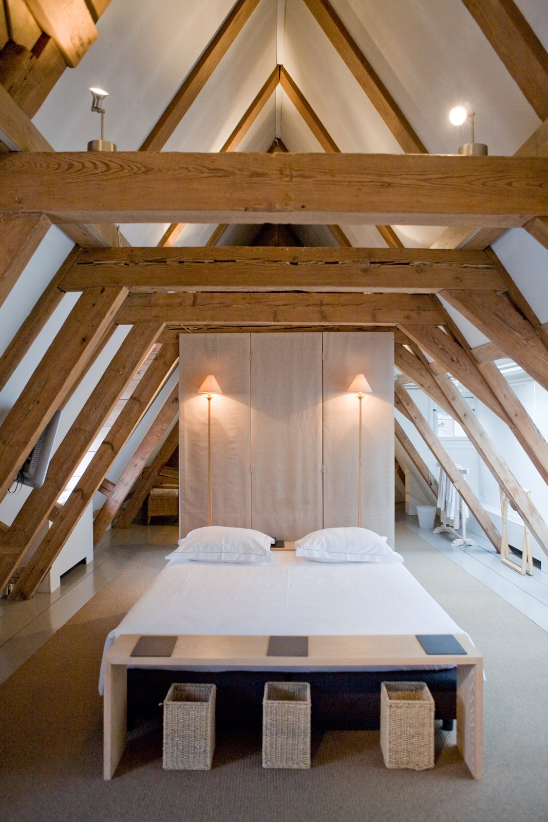 Giant wooden roof beams in the attic suite add to the peaceful and minimalist space.  Photo 8 of 11 in 10 Bright and Airy Modern Attic Renovations