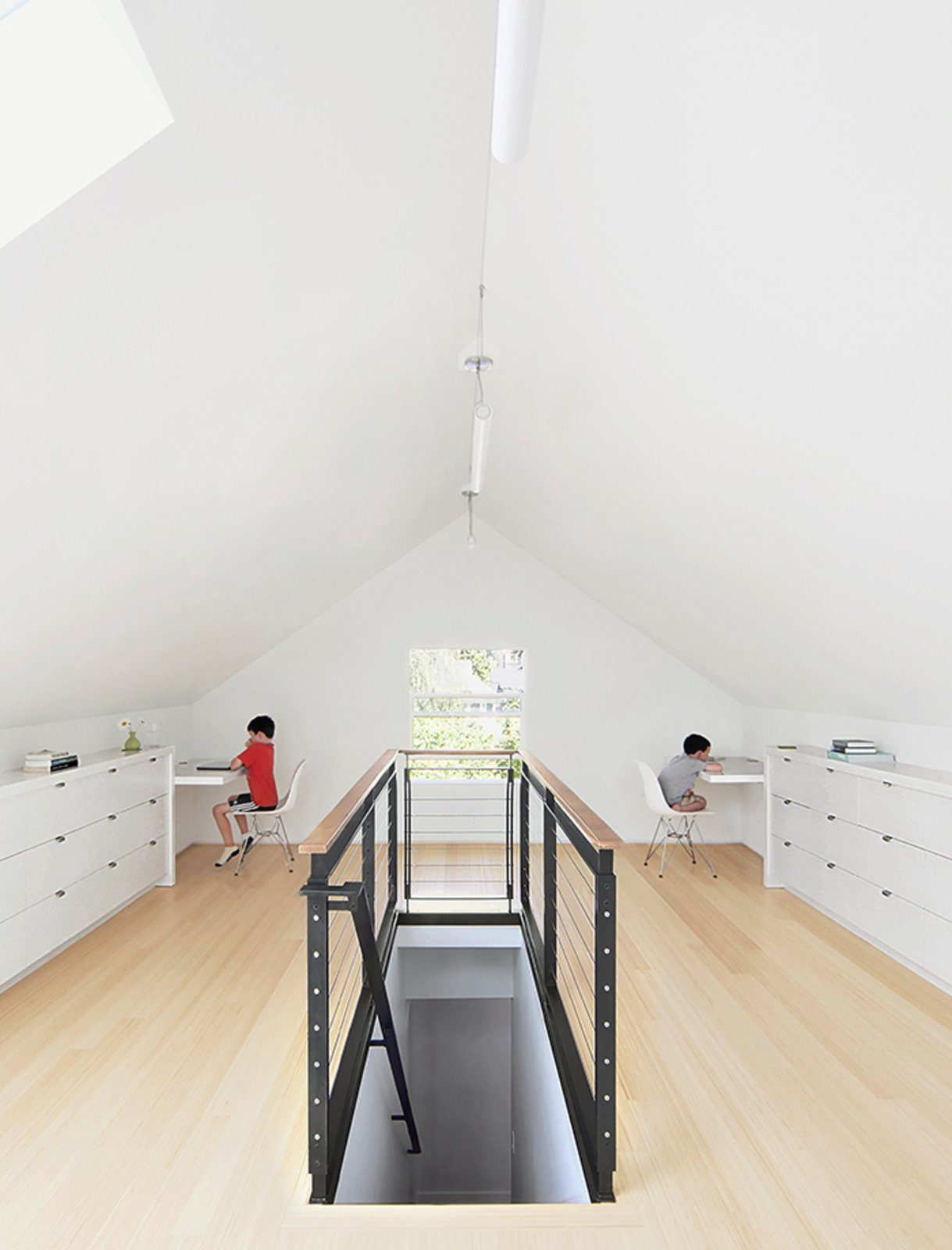 Bamboo flooring and custom built-ins—fashioned from medium-density fiberboard with a white-lacquer finish—brightened the 650-square-foot attic. The custom-designed  blackened-steel balustrade has cable inserts and a walnut handrail.  Photo 11 of 11 in 10 Bright and Airy Modern Attic Renovations