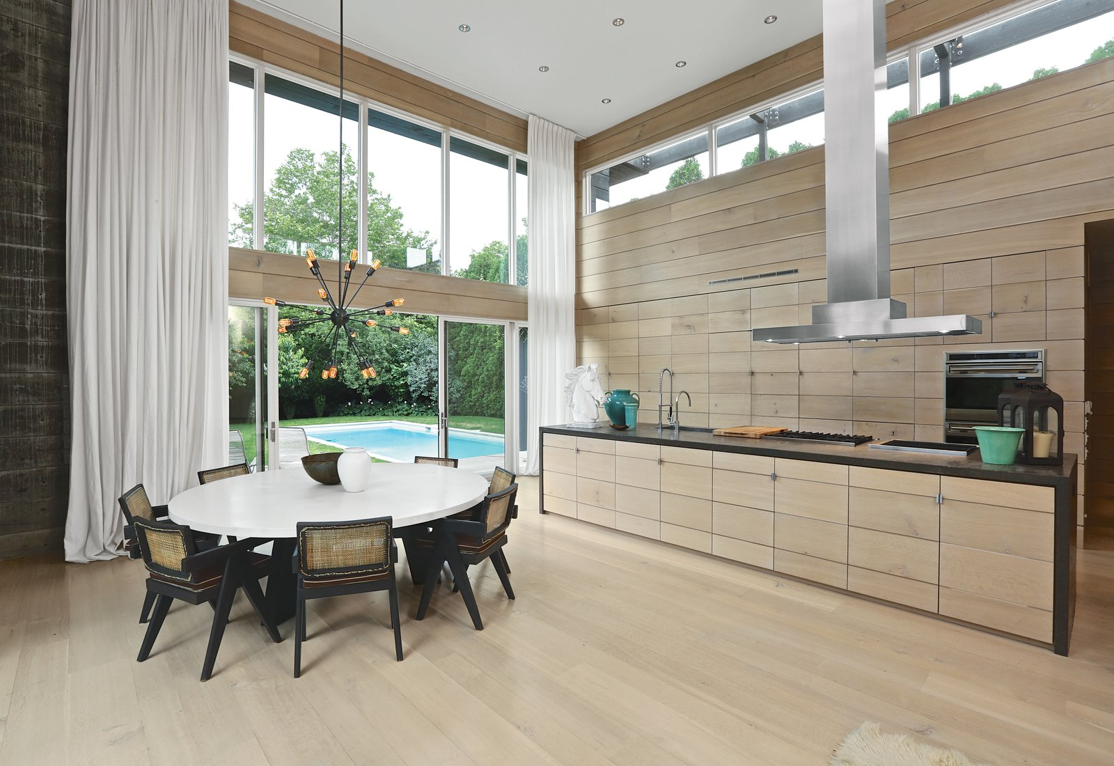 A Sputnik chandelier in aged steel from Restoration Hardware hangs above a custom concrete-topped table. The vintage cane-and-teak dining chairs were designed in 1966 by Pierre Jeanneret. In the kitchen, a brushed stainless steel range hood by Modern-Aire is matched with faucet hardware from Dornbracht, a Blanco sink, Viking rangetops, and built-in ovens by Wolf. Recessed lighting overhead uses LED bulbs set in Juno housing.  Photo 7 of 11 in Spotted: 10 Modern Homes in the Hamptons