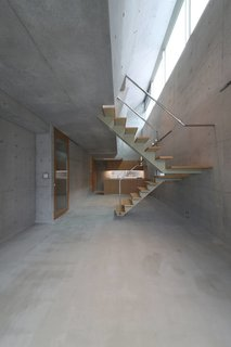 The interior consists entirely of exposed concrete that's accented by wood. The ground floor features double-height ceilings that maximize natural light from the light wells above.