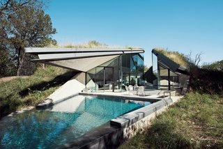 The concrete, steel, and glass house is divided into two distinct public and private halves.