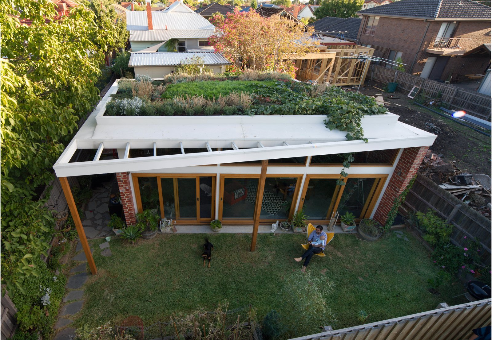 Exterior, House Building Type, and Green Roof Material Emilio Fuscaldo sits in the garden outside the brick house that he designed for himself and his partner, Anna Krien, on a small subdivided lot in Coburg, a suburb north of Melbourne, Australia.  Photos from These 10 Green Roofs Bring Life—and So Much More—to These Modern Structures