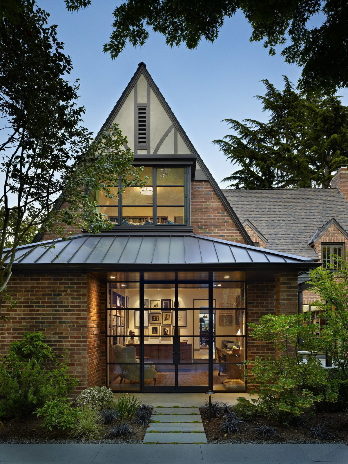 This whole-house remodel gives a venerable brick Tudor home a modern twist. Designed for two book (and dog!) lovers, it incorporates bookshelves and cozy seating areas throughout the house. Modern details complement traditional elements while steel windows, doors and exposed structure open the interior to light and views. The exterior features a 'secret garden', sunroom and terrace that overlook Lake Washington.  Photo 5 of 12 in 11 of Our Favorite Pacific Northwest Homes From the Community