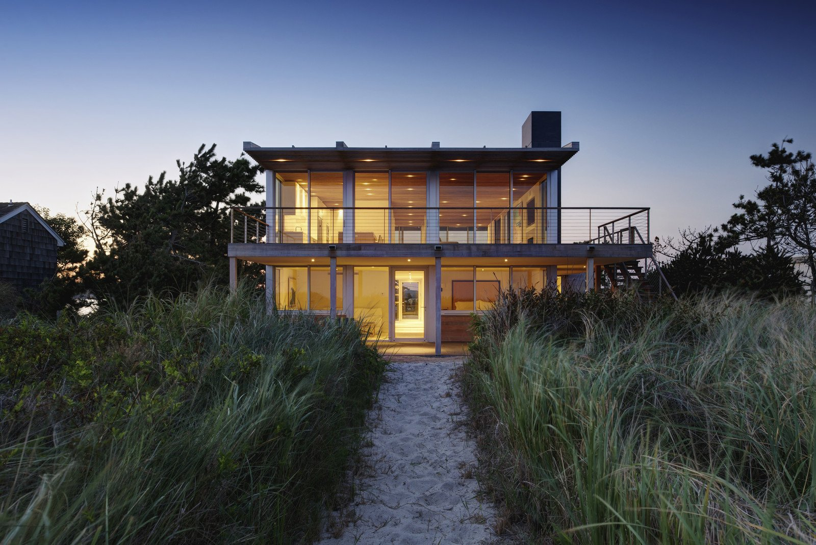 Perched atop the crest of the dune between the ocean and bay, this home in the Hamptons utilizes elegant materials which were chosen for their simplicity, sustainability, low maintenance and ability to coexist with the sea, sand and vegetation of the site. The use of glass also provides the residents with stunning views of their surroundings.   <span style=  Photo 4 of 11 in Glass Takes Center Stage in These 10 See-Through Homes