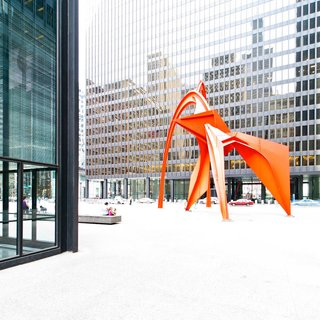 """The Chicago Federal Center is another example of the incredible architectural legacy that Mies van der Rohe left the city of Chicago. In his book Chicago: In and Around the Loop, Walking Tours of Architecture and History, Gerard Wolfe refers to the Federal Center as """"the ultimate expression of the second Chicago school of architecture."""" Alexander Calder's striking 'Flamingo' sculpture complements the linear complex."""