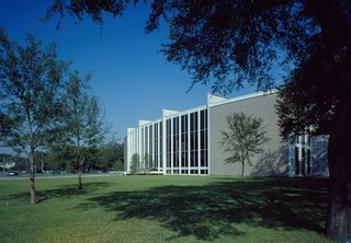 """In 1953, Nina J. Cullinan gifted a building addition to Houston's Museum of Fine Arts as a memorial for her parents. Her only stipulation was that it had to be designed by an architect of """"outstanding reputation and wide experience."""" After being selected for the commission, Mies arrived in Houston on a hot summer day and rejected the idea of a standard open museum courtyard by remarking, """"But in this climate, you cannot want an open patio."""""""