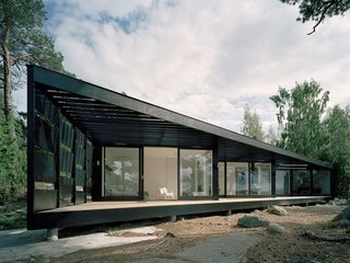 A light-weight building in glass and wood, this summerhouse in the Stockholm archipelago has been inspired by its location with its dark wood exterior and abundance of windows to take in the stunning view.