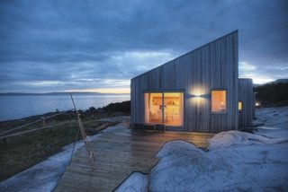 Designed by TYIN tegnestue Architects and built by the owners themselves, this cottage celebrates traditional back-to-nature elements in traditional Norwegian culture. Situated amidst marshland, sea-adjacent rock, and scattered pine-and-juniper vegetation, careful consideration was made to protect the sensitive surrounding terrain. Only 328 feet from the sea, some marsh had to be cleared while preparing for the construction, exposing bedrock—which integrated the cottage into the landscape.