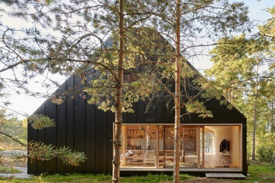 Nestled in a forest of tall pines in the Stockholm Archipelago, the exterior of this island home is clad entirely in folded black sheet metal. Three glazed sliding doors with hardwood frames provide entrances and direct access to the outdoor areas.