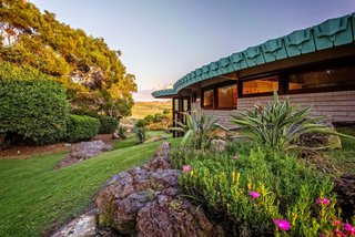 The only Frank Lloyd Wright–designed home in Hawaii captures not only the architect's signature style, but also the spirit of its location—with an outdoor lava-rock hot tub overlooking the ocean and breathtaking, panoramic mountain views of three of the Big Island's awe-inspiring volcanoes (Mauna Kea, Mauna Loa, and Hualalai). The 1995 home was commissioned by Sanderson Sims in partnership with Taliesin Associated Architects, John Rattenbury, and the Frank Lloyd Wright Foundation. Originally conceived for the Cornwell Family in Pennsylvania in 1954, the 3,700-square-foot, passive solar hemicycle home embodies the architect's principles of organic architecture in which the structure blends harmoniously with the natural landscape.