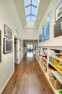 Upstairs, there are three bedrooms, customized and spacious closets, a children's bathroom, a family room, and a craft and music room overlooking the yard. The high-ceilinged hallway is brightened by natural light via a skylight which extends over the length of the passage.