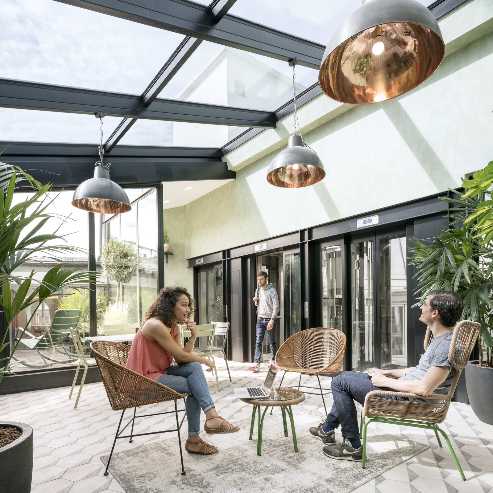 Stepping out of the elevator on the 6th floor, visitors are transported into a luminous, vegetation-filled solarium.  Photo 2 of 14 in Take a Peek Inside Airbnb's New Loft-Inspired Office Space in Paris