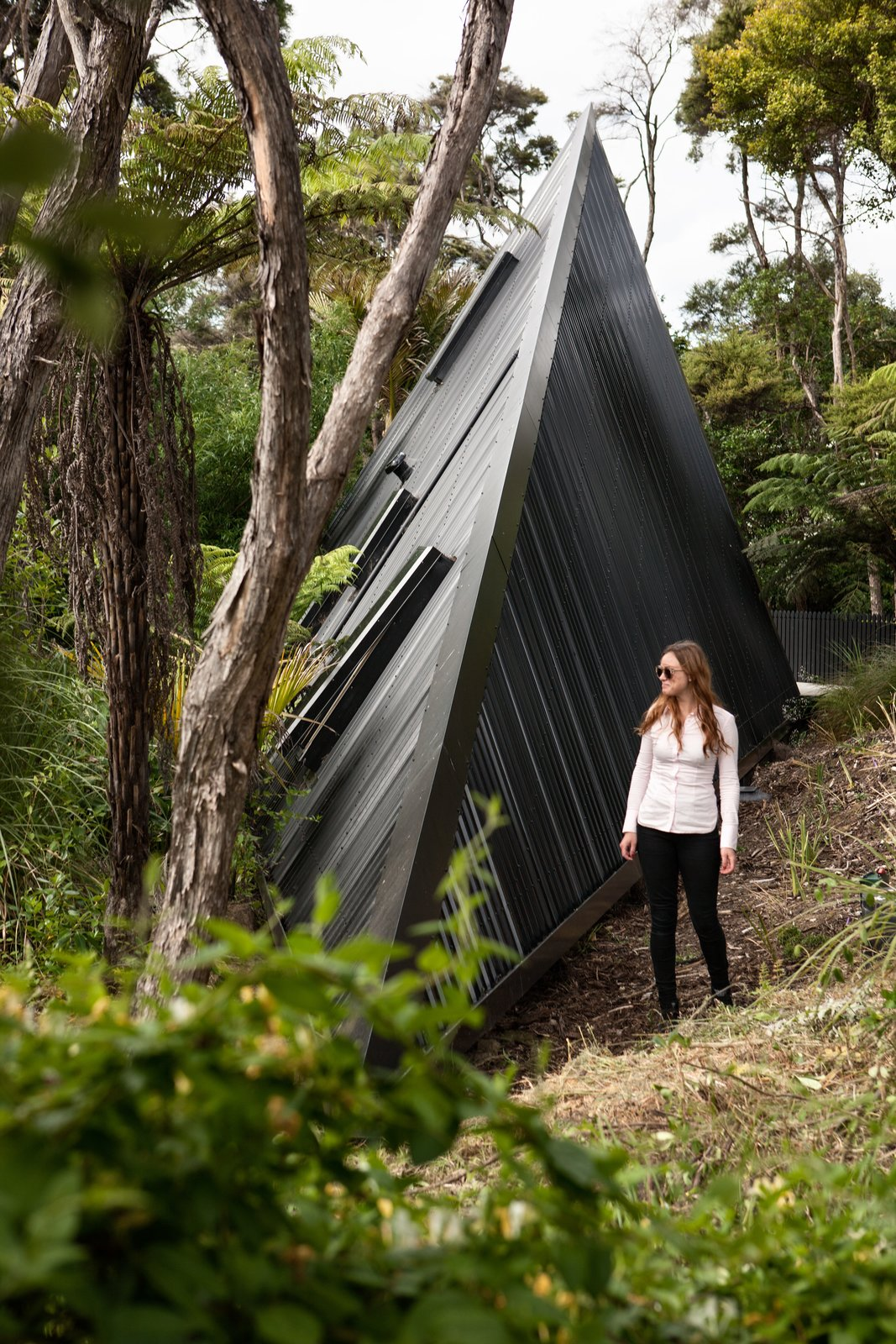 Outdoor, Trees, Back Yard, and Shrubs Set in the New Zealand rain forest, the Tate has landscaped the site with hundreds of plants exclusive to New Zealand to recreate a natural native forest landscape.  Photo 7 of 8 in Stay in a Tent-Inspired A-Frame Cabin in the New Zealand Rain Forest