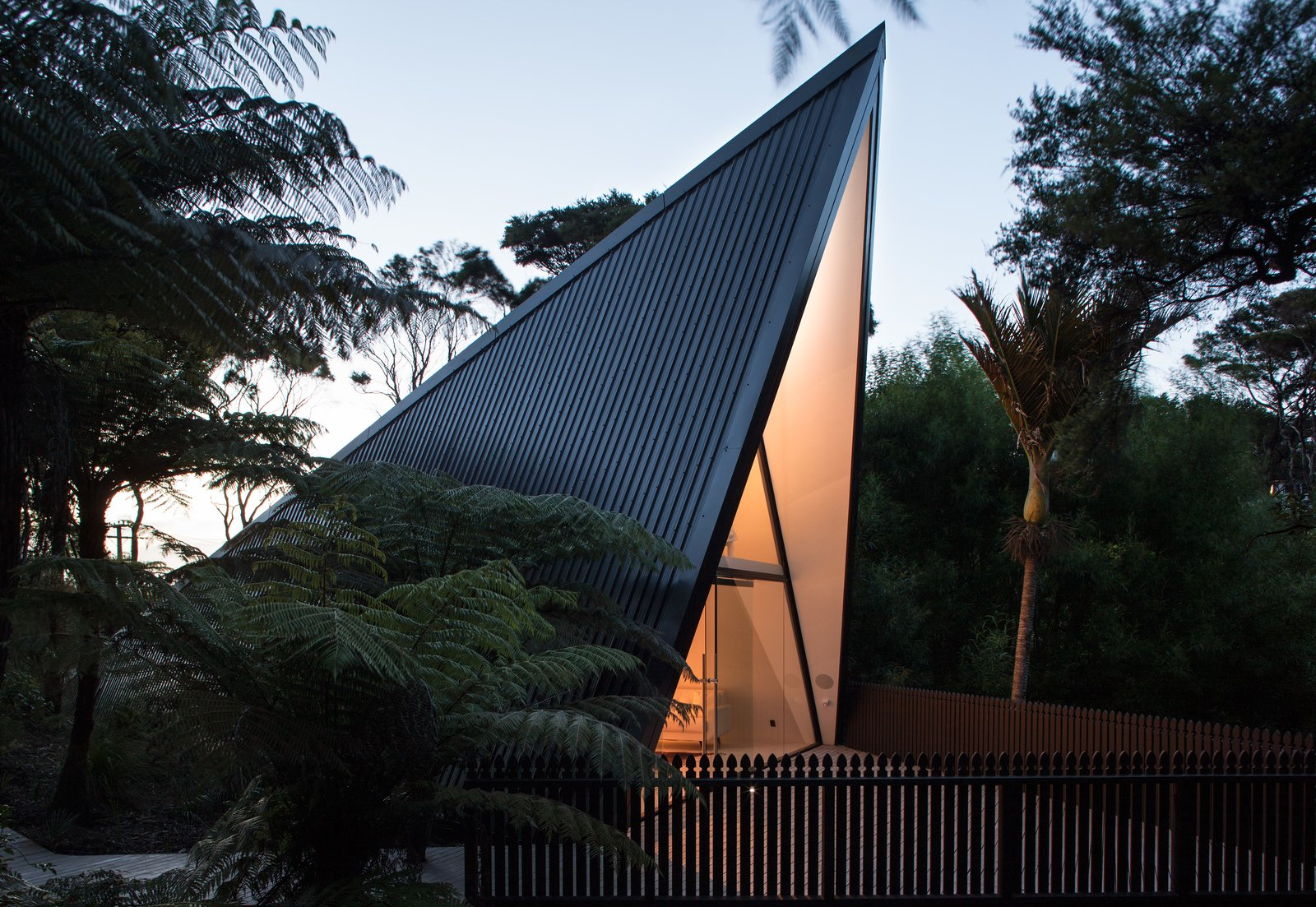 Trees, Small, Wood, Front Yard, Vertical, Exterior, House, and Metal The front deck was designed to  Best Exterior Vertical Photos from Stay in a Tent-Inspired A-Frame Cabin in the New Zealand Rain Forest