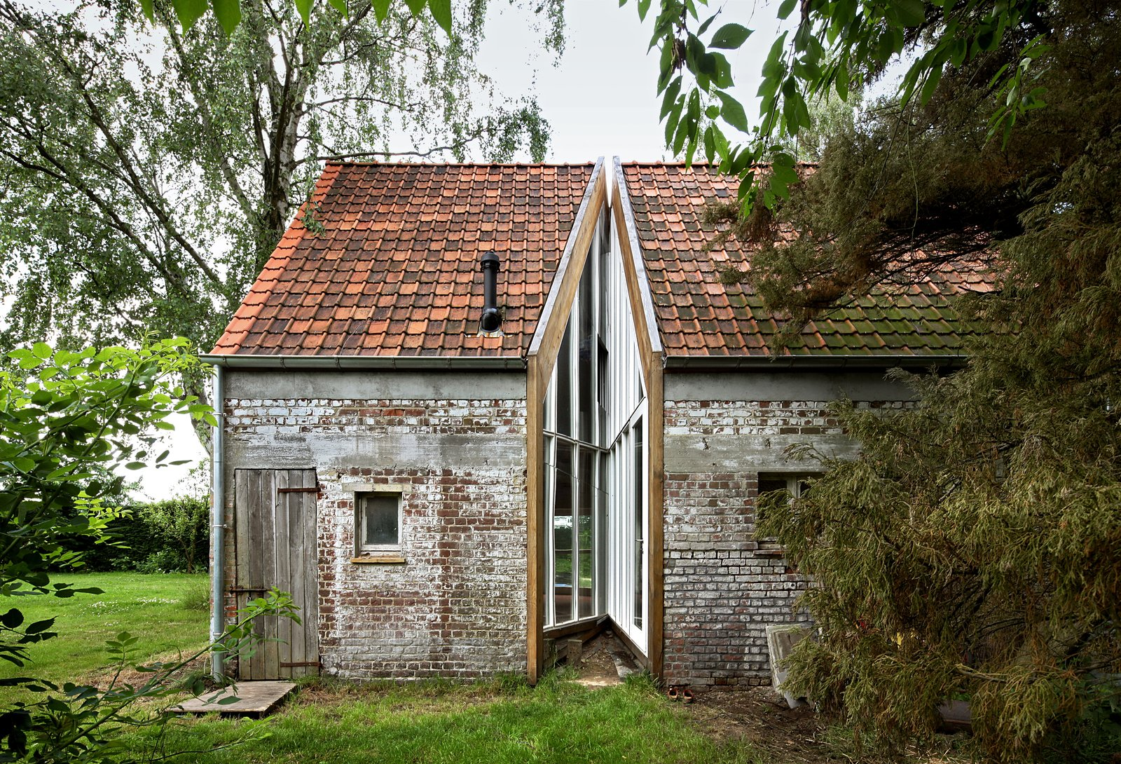 For this old farm building in the back garden of a larger set of farm buildings in Flanders, Belgium, Architecten de Vylder Vinck Taillieu converted this original structure into a modern home for the family's daughters. The simple incision of glass and mirrors brings light and successfully divides the space inside into separate rooms.  Photo 13 of 17 in A New Book Examines the Art of Breathing Life Into Forgotten Architecture