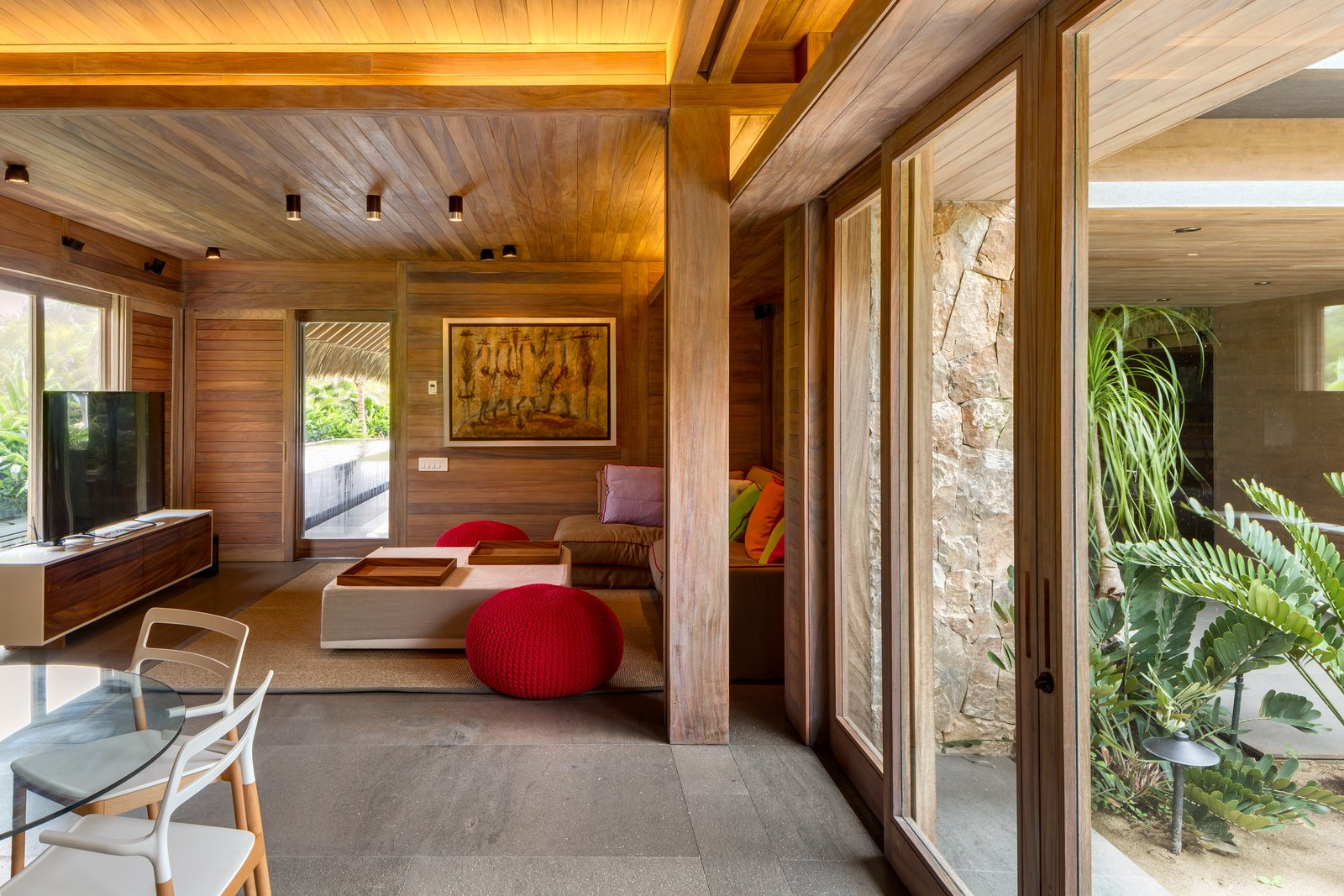Living Room, Sofa, Ottomans, Coffee Tables, Ceiling Lighting, Cement Tile Floor, Chair, and Console Tables The material palette includes naturally finished local parota wood and rough-cut stone.  Photo 11 of 14 in This Expansive Beachside Home on Mexico's Pacific Coast Puts a Modern Spin on Tradition