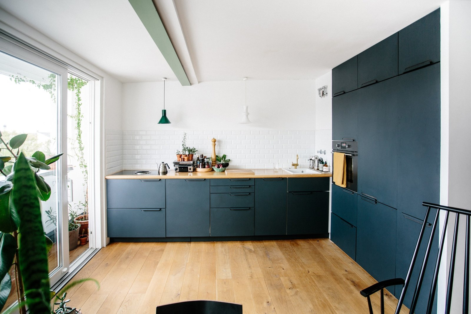 Kitchen, Wood Counter, Wood Cabinet, Light Hardwood Floor, Pendant Lighting, Wall Oven, Vessel Sink, Subway Tile Backsplashe, and Cooktops Danish architect Sigurd Larsen needed a new kitchen for his 90-square-meter apartment in the hip Kreuzberg district of Berlin—so he designed his own in collaboration with Reform. Larsen opted for a kitchen in anthracite—as the darker color added contrast to his oak floors and  countertops.  Photo 2 of 9 in Modern Kitchen Upgrade Ideas From a Danish Design Firm That's Challenging the Kitchen Market