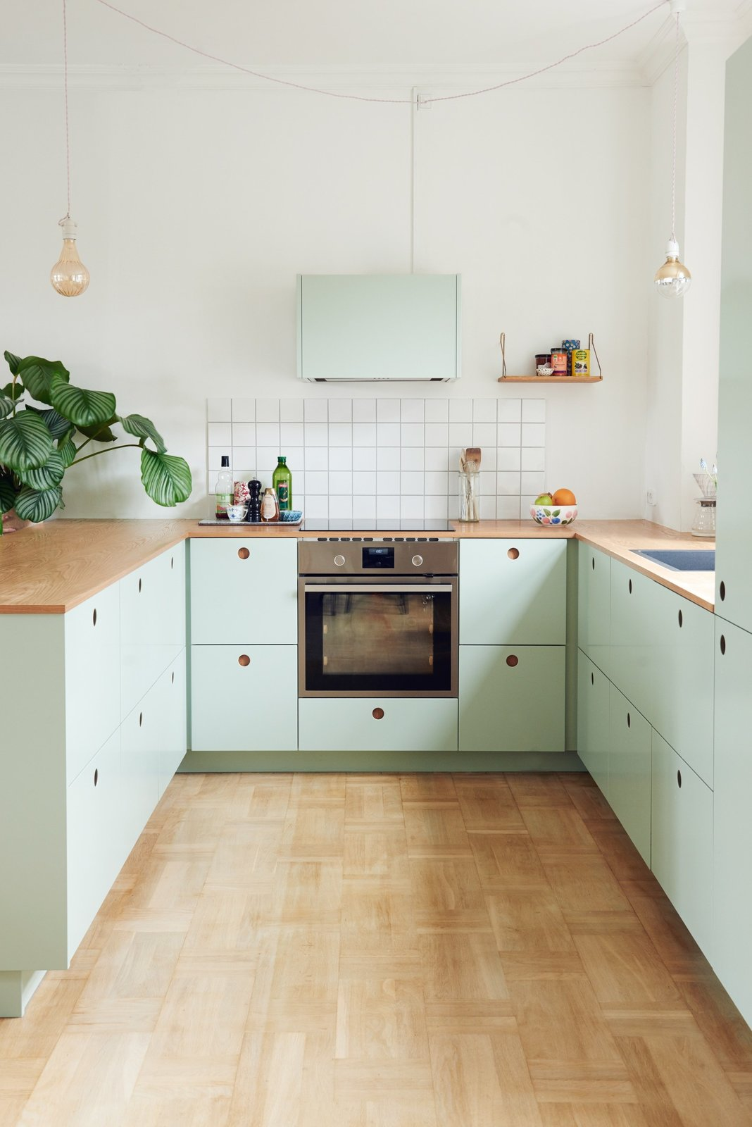 Kitchen, Wood Counter, Light Hardwood Floor, Pendant Lighting, Subway Tile Backsplashe, Wall Oven, Range Hood, Drop In Sink, Colorful Cabinet, and Cooktops Danish blogger, Tikkie Elsøe, chose mint green  Best Photos from Modern Kitchen Upgrade Ideas From a Danish Design Firm That's Challenging the Kitchen Market