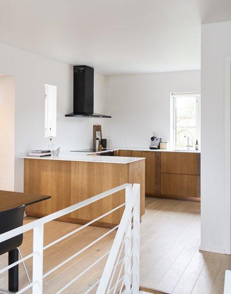 Henning Larsen Architects' kitchen design in oak veneer with a copper strip. Countertop in white Corian.