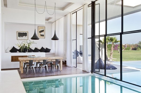 An indoor/outdoor swimming pool flows into the living space and grand, floor-to-ceiling windows lead onto a large, semi-covered terrace with stunning views of the Atlas Mountains.