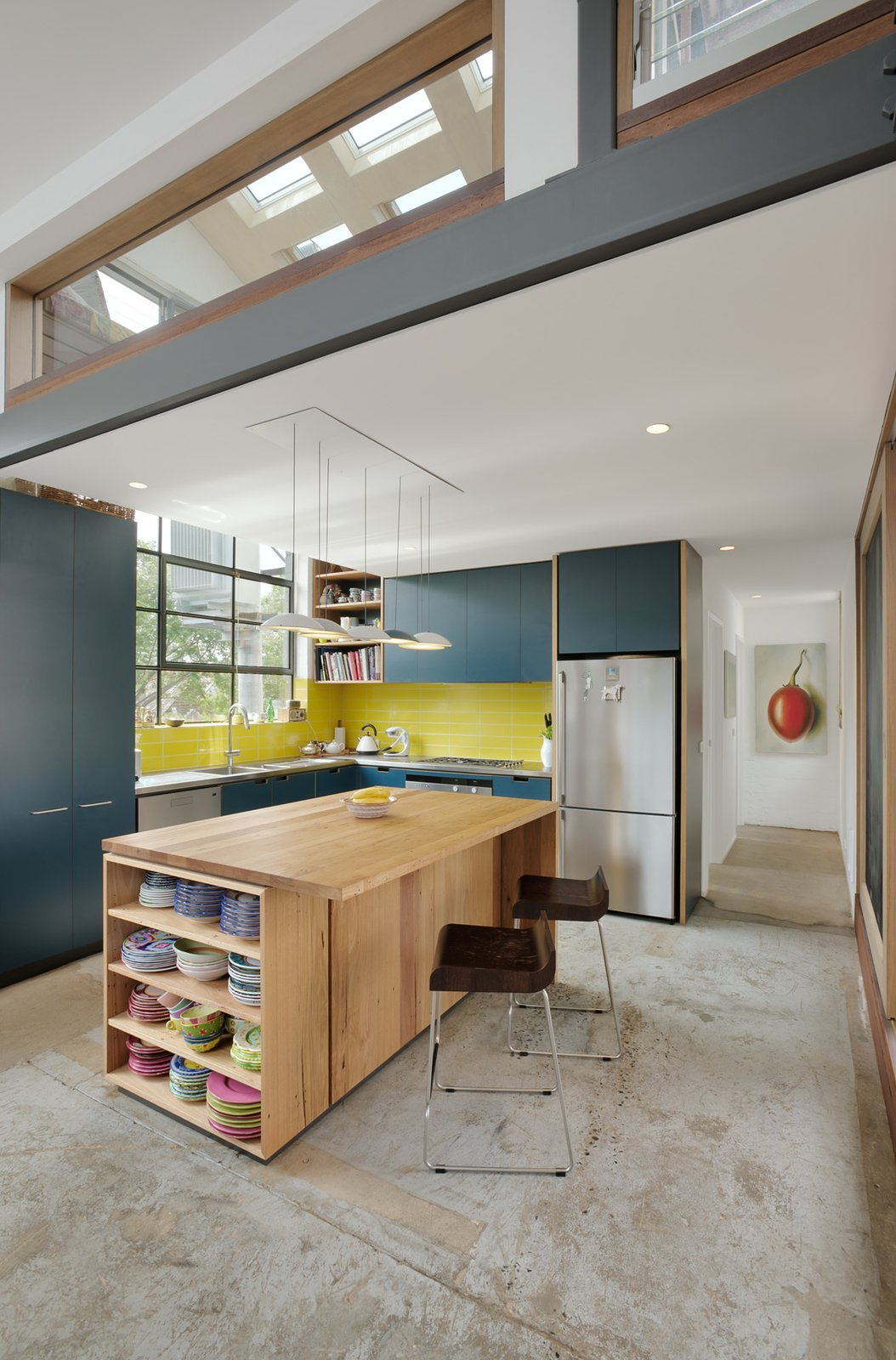 Kitchen, Colorful, Concrete, Subway Tile, Pendant, Recessed, Ceiling, Refrigerator, Dishwasher, Wall Oven, Range, Drop In, and Wood A family's dream of living in a converted warehouse becomes a reality when Zen Architects successfully transforms a leaky warehouse from the 1960s into a bright and airy family home—without compromising on comfort or energy efficiency. Bright yellow subway tiles complement dark teal cabinets and colorful dishware.  Best Kitchen Recessed Pendant Wall Oven Wood Subway Tile Photos from A 1960s Melbourne Warehouse Is Upcycled and Transformed Into an Energy-Efficient Family Home