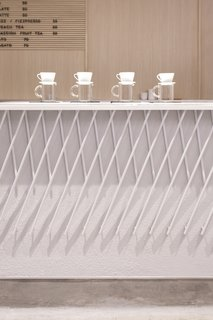 The front of the coffee bar features a decorative armor made out of angled pieces of white-painted metal that form a criss-cross pattern.