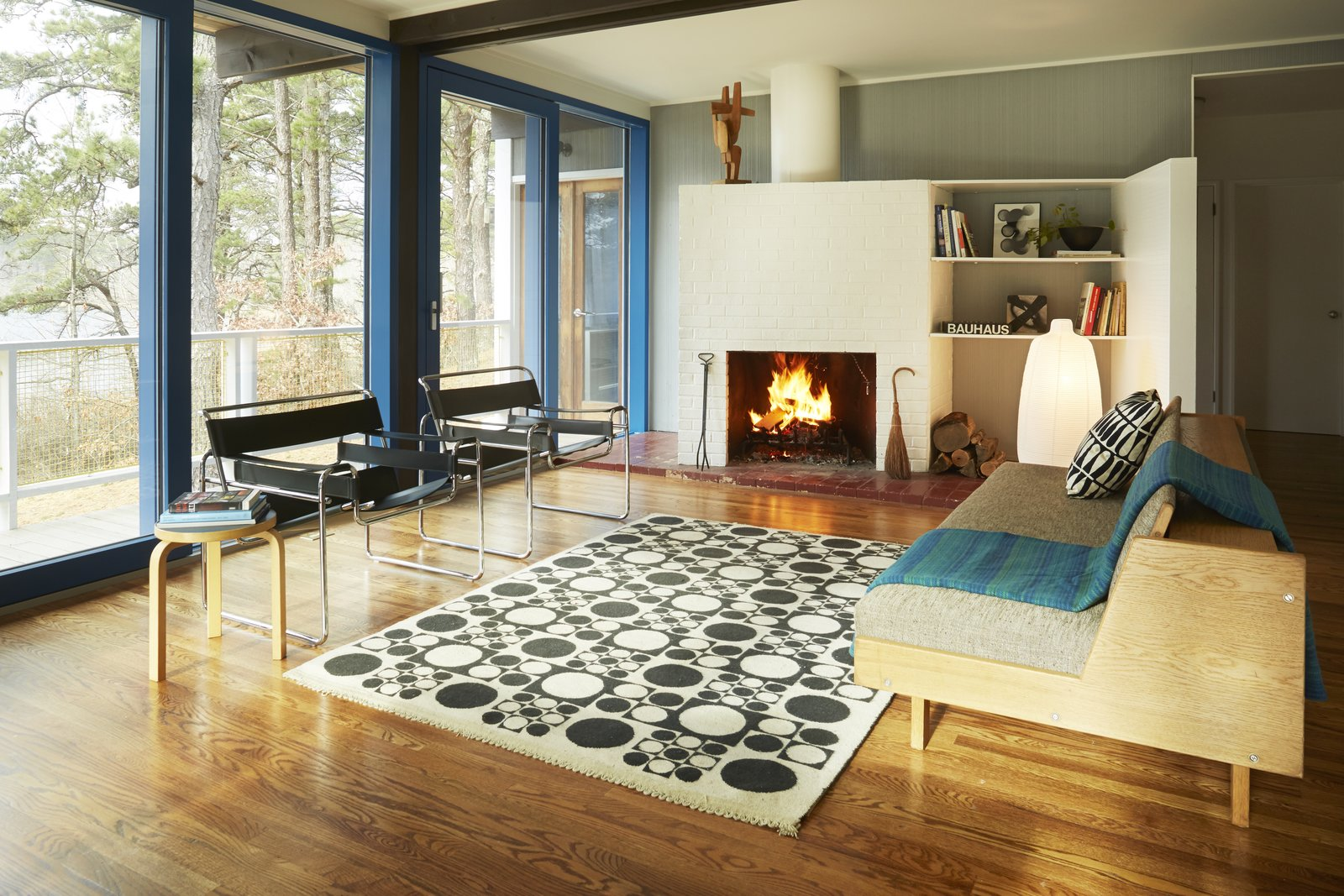 Living Room, Chair, Sofa, End Tables, Floor Lighting, Standard Layout Fireplace, Wood Burning Fireplace, Medium Hardwood Floor, and Rug Floor The living area has been lovingly restored.  Photo 5 of 9 in Experience Cape Cod Modern by Staying at the Midcentury Weidlinger House