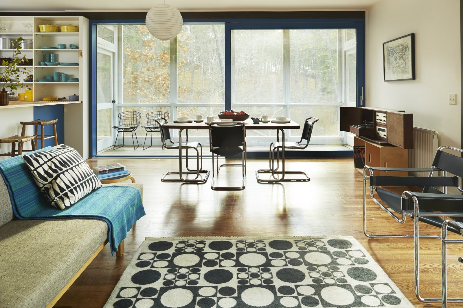 Light Hardwood Floor, Rug Floor, Media Cabinet, Sofa, Chair, Stools, Dining Room, Table, Shelves, and Pendant Lighting The living area has been lovingly restored.  Photo 7 of 9 in Experience Cape Cod Modern by Staying at the Midcentury Weidlinger House