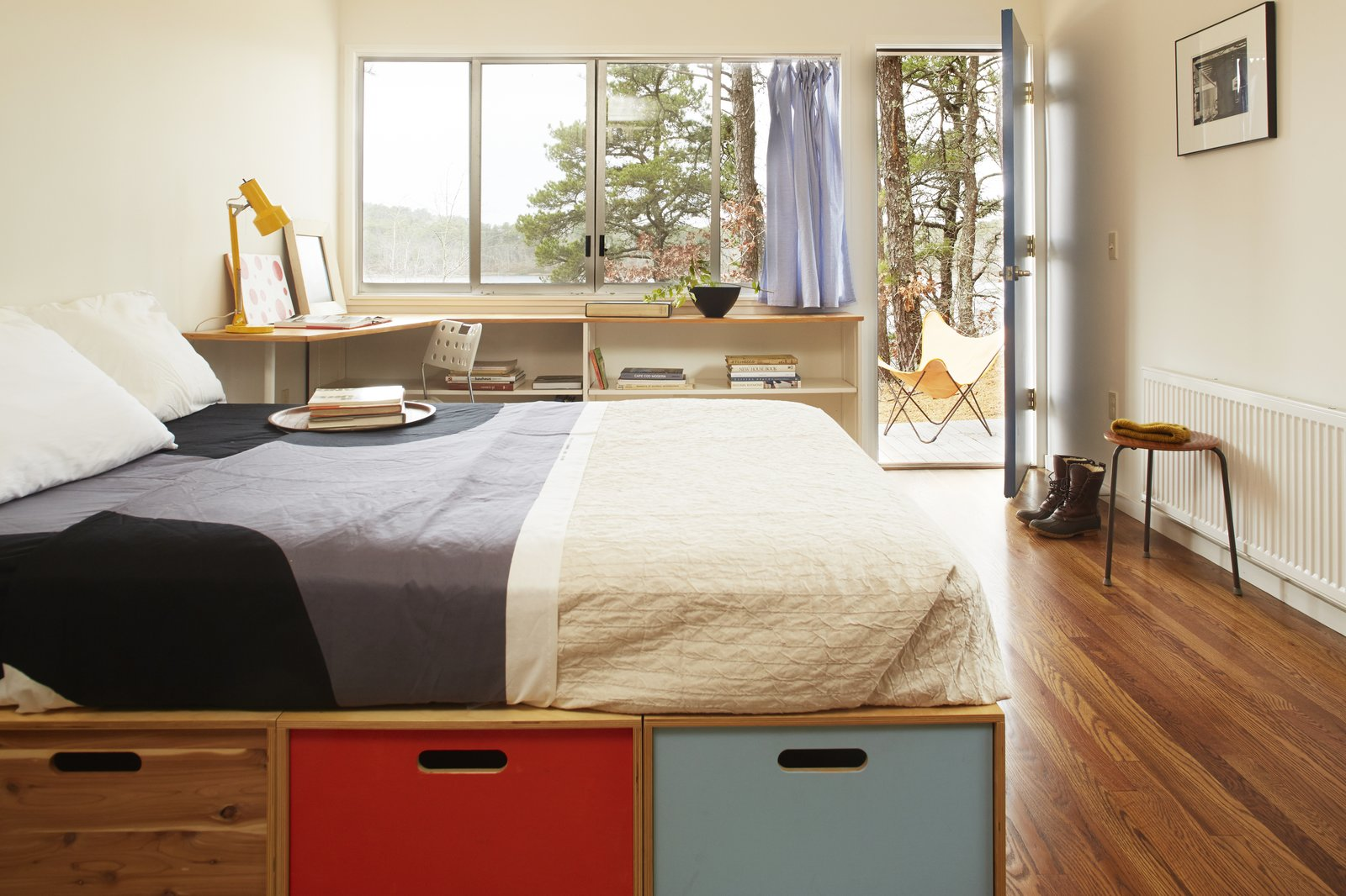 Bedroom, Shelves, Bed, Storage, Lamps, Table Lighting, and Medium Hardwood Floor The bedroom zone has fairly enclosed stud-walls.  Photo 9 of 9 in Experience Cape Cod Modern by Staying at the Midcentury Weidlinger House