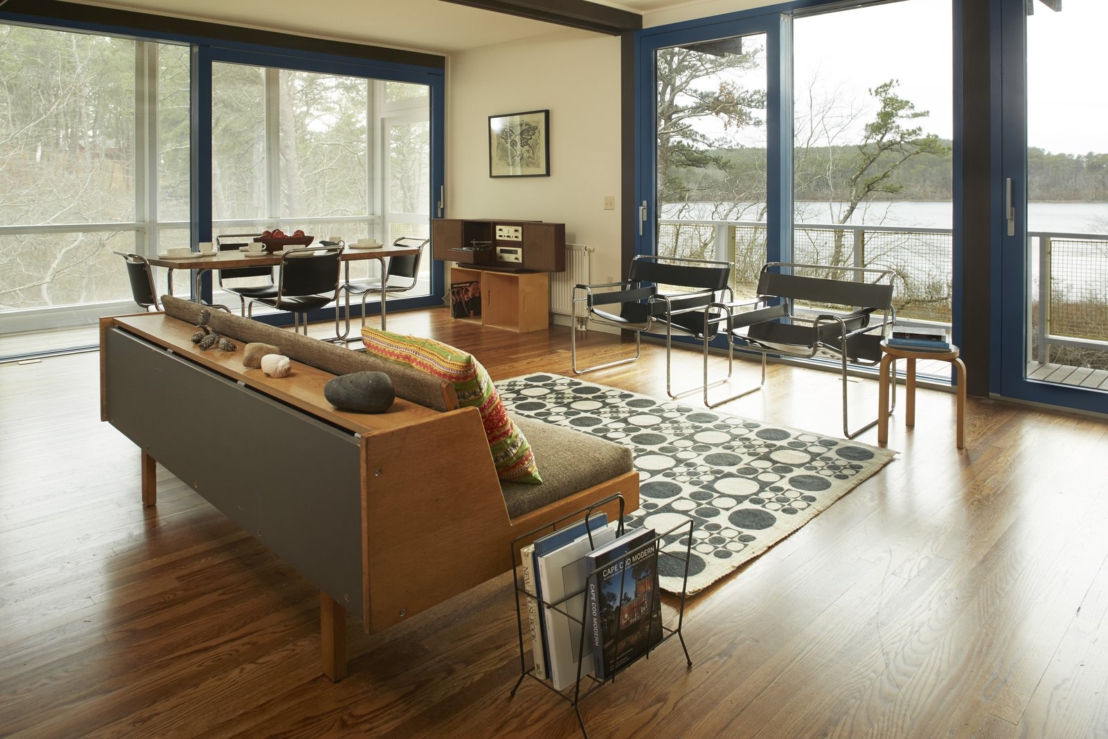 Living Room, Sofa, Chair, Table, Stools, Storage, Media Cabinet, Medium Hardwood Floor, and Rug Floor The home is perched above the pond and features stunning views of the natural surroundings.  Photo 6 of 9 in Experience Cape Cod Modern by Staying at the Midcentury Weidlinger House