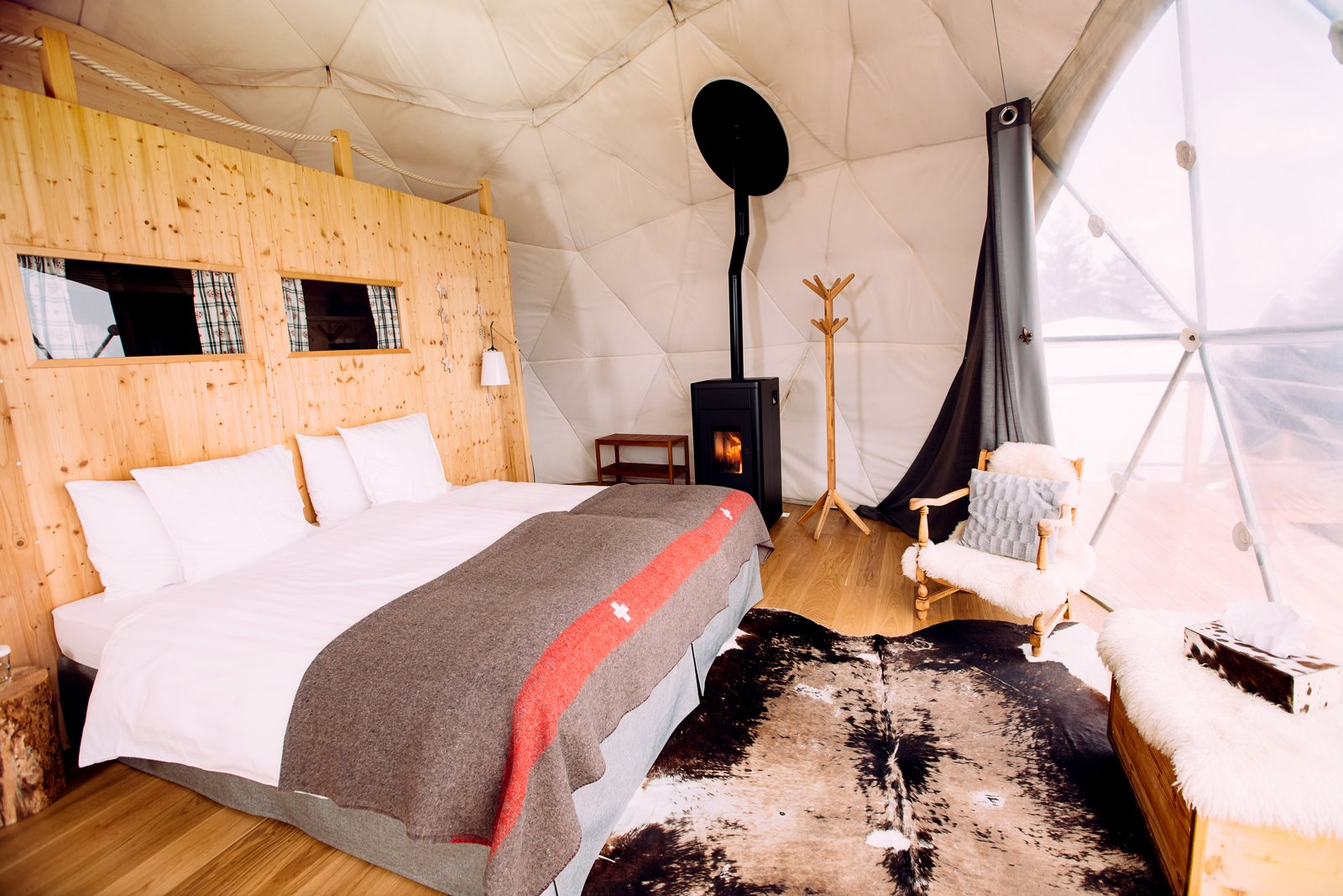 Bedroom, Chair, Medium Hardwood Floor, Lamps, Rug Floor, Bed, Storage, Wall Lighting, and Night Stands All the pods are equipped with organic bedding and efficient pellet wood‑burning stoves adding to the cozy interiors.  Photo 4 of 11 in Go Eco-Friendly Glamping in These Geodesic Domes in the Swiss Alps