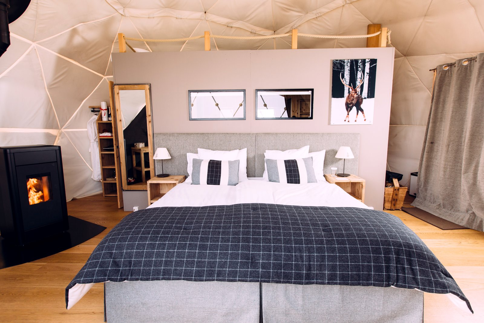 Bedroom, Medium Hardwood Floor, Bed, Night Stands, and Table Lighting Whitepod currently offers 15 pods in 3 different configurations.  Best Photos from Go Eco-Friendly Glamping in These Geodesic Domes in the Swiss Alps