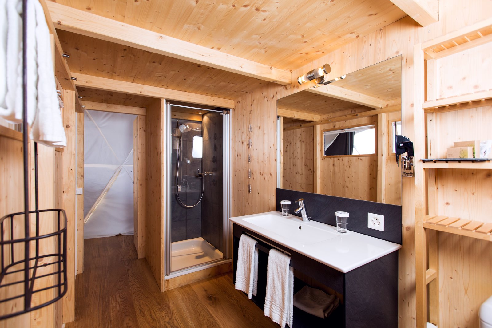 Bath Room, Medium Hardwood Floor, Enclosed Shower, Wall Lighting, and Drop In Sink Each pod is conveniently equipped with a complete bathroom.  Photo 7 of 11 in Go Eco-Friendly Glamping in These Geodesic Domes in the Swiss Alps