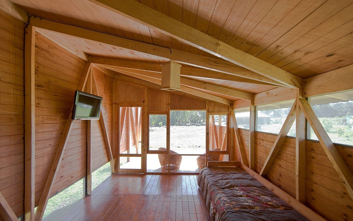 The banks of windows on either side of the huts illuminate the interiors and allow for natural cross ventilation. Tagged: Bedroom, Bed, Chair, Medium Hardwood, and Ceiling.  Best Bedroom Bed Medium Hardwood Photos from Experience the Magic of Easter Island While Staying in a Modern Eco-Cabana