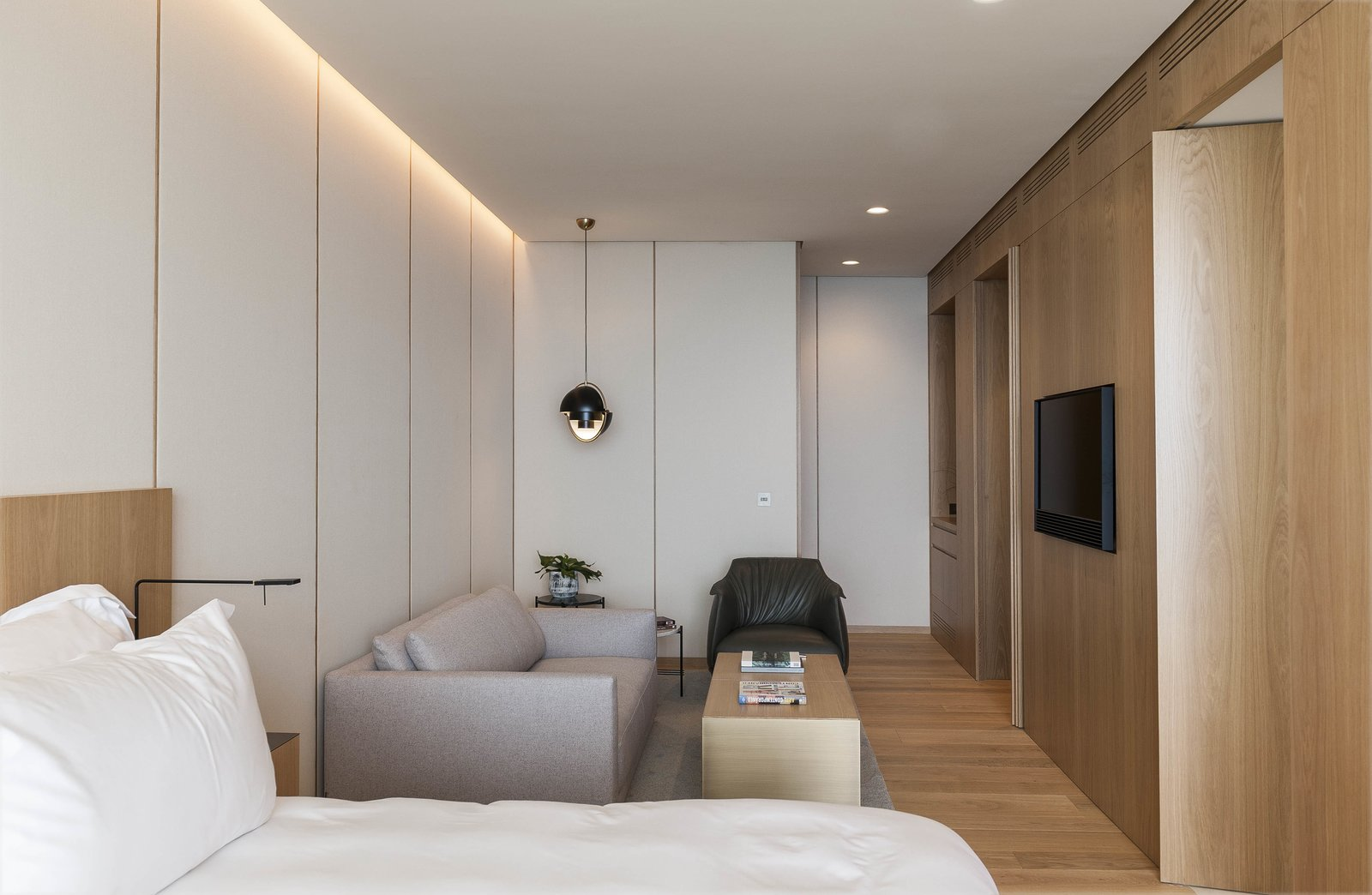 Bedroom, Chair, Bed, Pendant Lighting, Light Hardwood Floor, Table Lighting, Lamps, and Night Stands The warmth of the natural materials  Photo 9 of 13 in Spain's Basque Coast Gets a New Modern Hotel With a Michelin-Starred Restaurant
