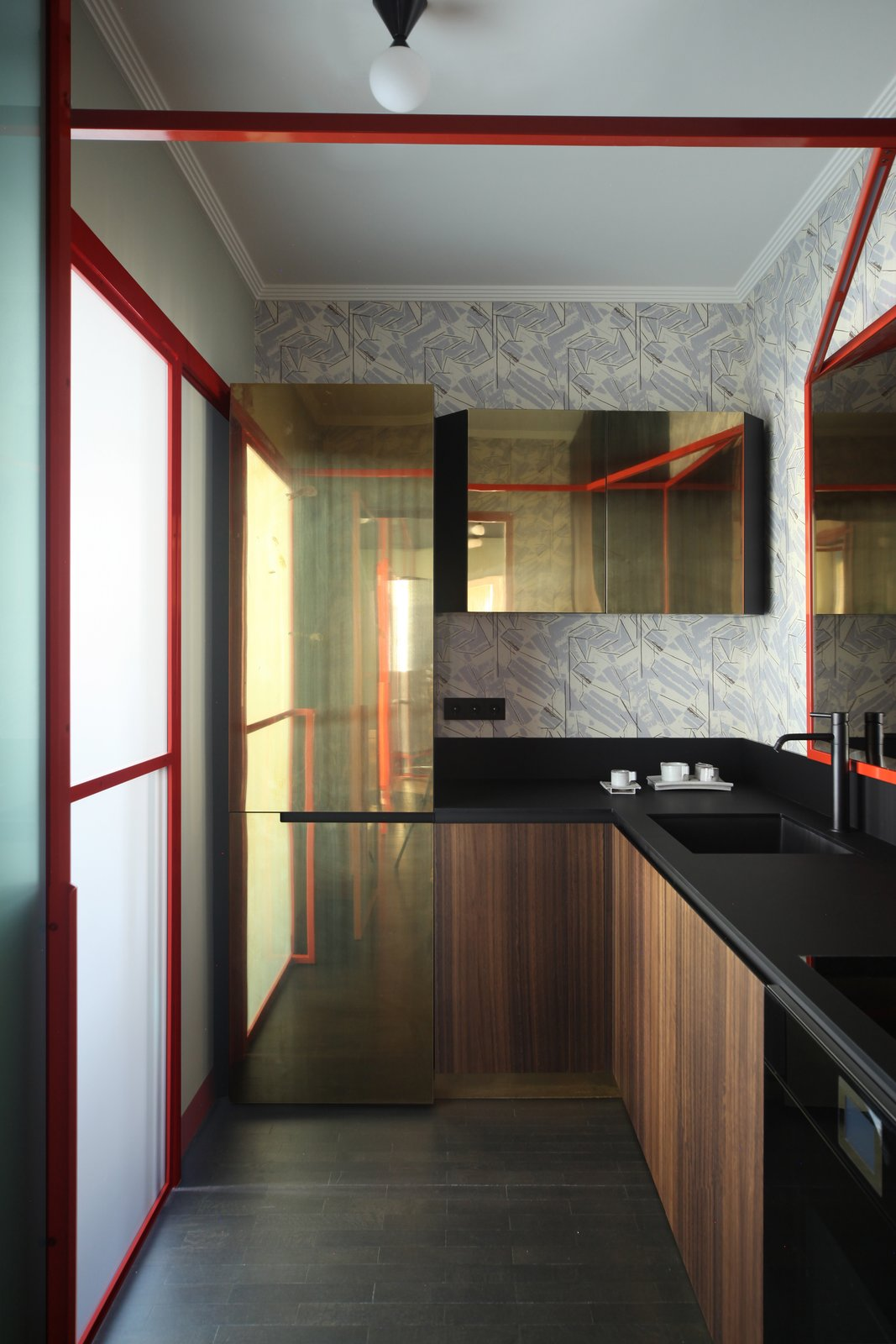 Kitchen, Laminate, Ceiling, Refrigerator, Drop In, Dark Hardwood, and Metal Kitchen: doors in eucalyptus wood and brass, countertop in high-thickness laminate Polaris by Abet, designed by Marcante-Testa, built by Materia Design and Om Project, faucets from Bellosta, lighting from Atelier Areti.  Best Kitchen Laminate Dark Hardwood Photos from This Venetian Apartment Is Bursting With Incredible European Furnishings