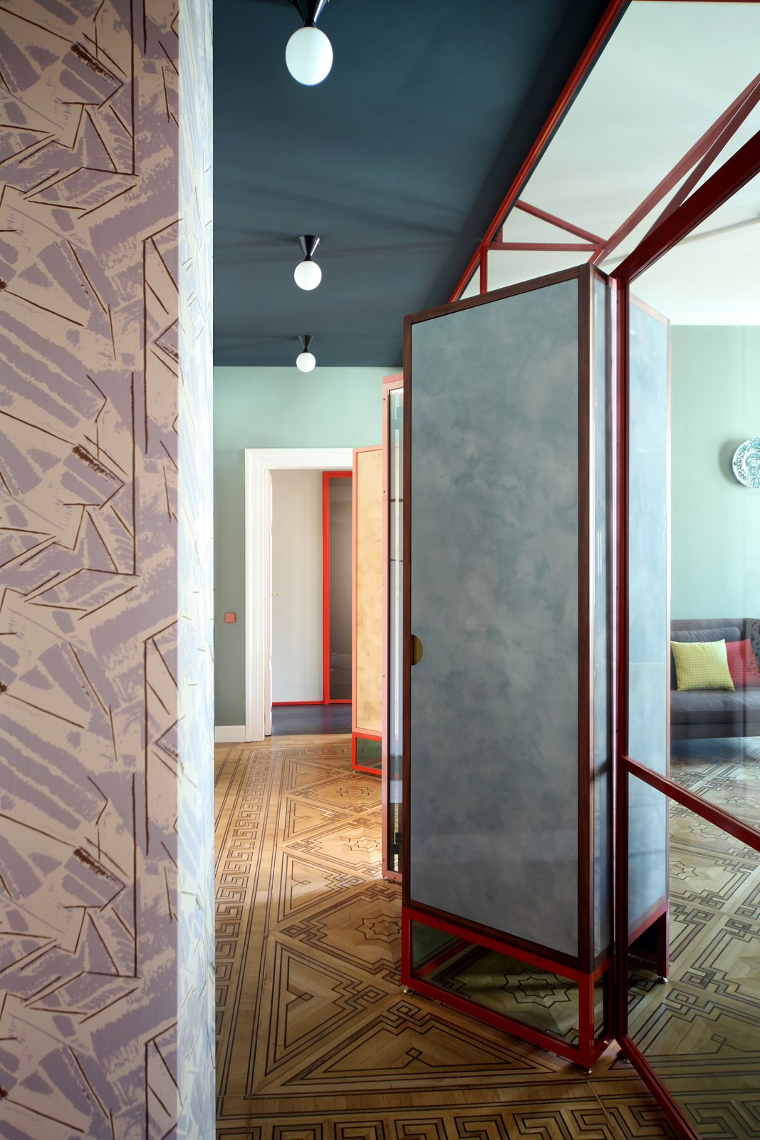 Hallway and Medium Hardwood Floor An initial partition creates a relationship between the entrance and the living room keeping the original design of the parquet flooring with inlaid  Photo 11 of 24 in This Venetian Apartment Is Bursting With Incredible European Furnishings