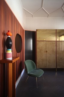 """This corner of the space features a Beetle dining chair by Gubi, a totem by Ettore Sottsass from Arts & Crafts Gallery in Venice, mirrors by Atipico. The incredible boisery consists of eucalyptus wood, glass, brass, lacquered iron, and """"stucco veneziano"""" by Marcante-Testa, built by Materia Design and Om Project. The Saraille wallpaper is by Designers Guild while the ceiling frames were designed by Marcante-Testa and built by Orseolo Restauri."""