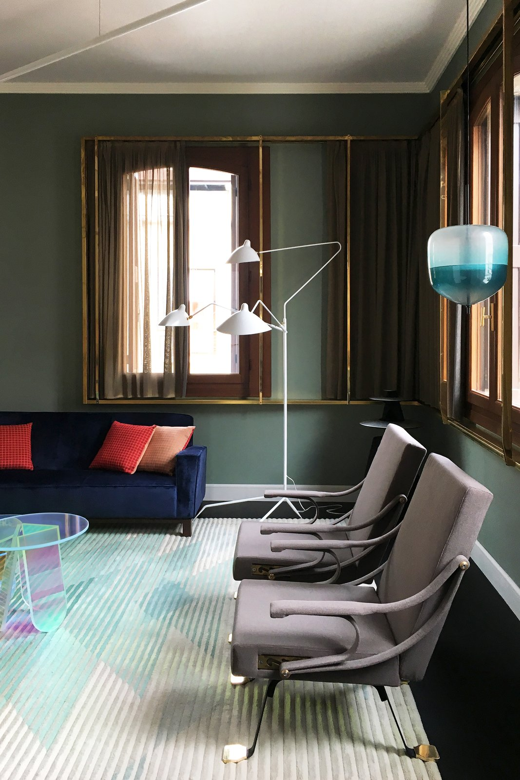 Living Room, Chair, Sofa, Lamps, Floor Lighting, Pendant Lighting, Coffee Tables, Rug Floor, and Carpet Floor This iconic floor lamp from Serge Mouille alongside the Flow S4 Pendant, designed by Nao Tamura, inspired by the reflections of the Venetian cityscape, are both stylish standouts.  Best Photos from This Venetian Apartment Is Bursting With Incredible European Furnishings