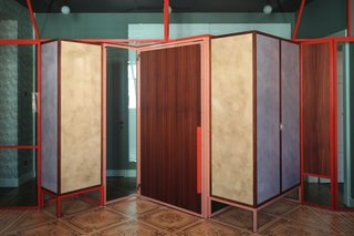 A metal-and-glass partition is set on the original wooden parquet and fitted with doors and cabinets, all designed by Marcante-Testa and built by Materia Design and Om Project.