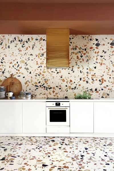 This colorful terrazzo makes a bold statement against the all-white cabinetry.