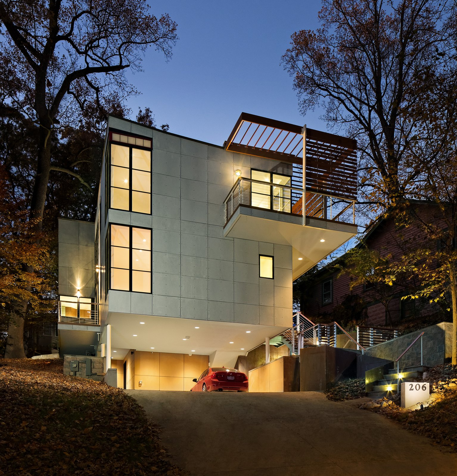 Exterior, House Building Type, and Concrete Siding Material The front of the house at night. An exterior stairway alongside the carport leads to the home's main entrance.  Photo 2 of 16 in An Airy, Award-Winning Maryland Gem Hits the Market