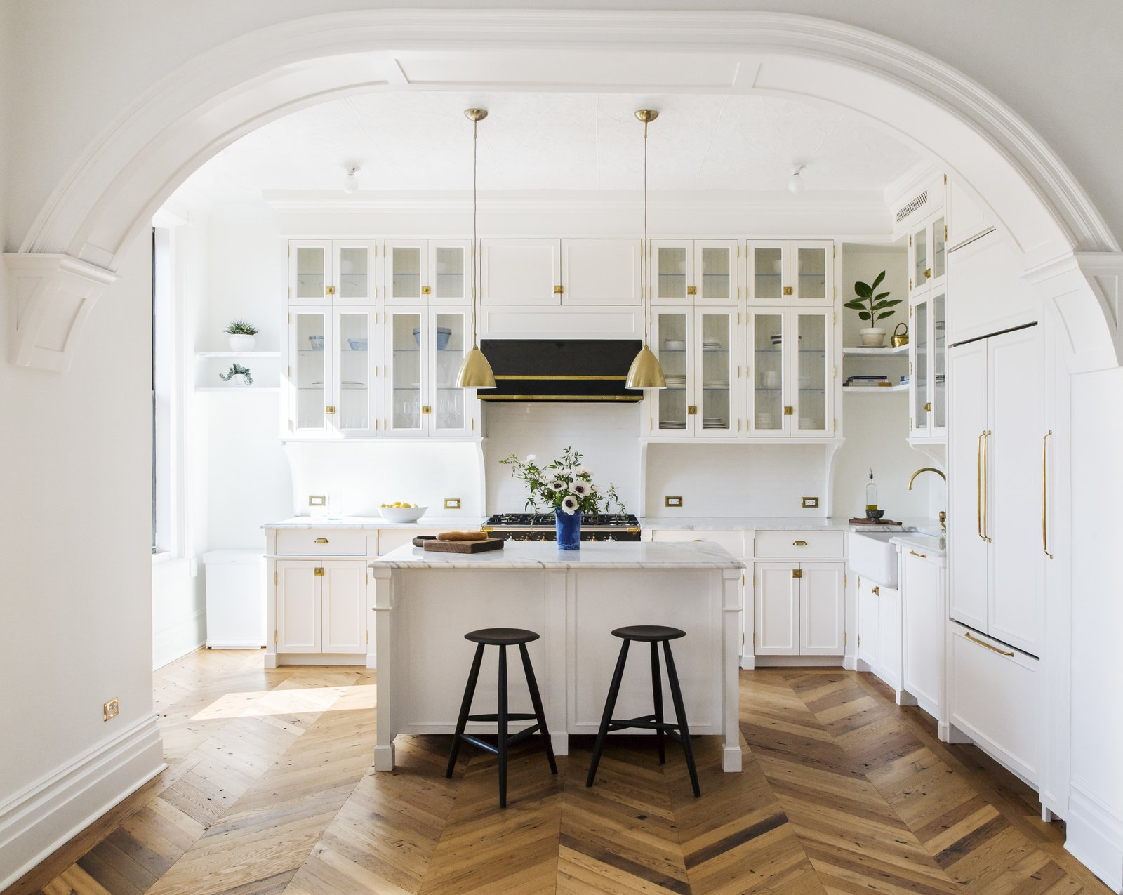 Kitchen, Range, Range Hood, Marble Counter, White Cabinet, Medium Hardwood Floor, Pendant Lighting, and Drop In Sink A kitchen island was added with bar stools from Sawkille and Bestlite Pendants from Gubi.  Photo 10 of 22 in A 19th-Century Schoolhouse in Brooklyn Becomes a Classy Apartment
