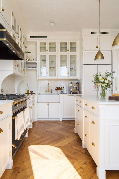 In this exquisite, classically styled black and white kitchen, gleaming white marble countertops and cabinets are juxtaposed by a dramatic, gold-trimmed black oven and range hood. Two Bestlite Pendants from Gobi enhance the gold details throughout this kitchen, a favorite among black and white kitchens.