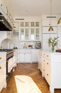 """There's a nice tension that exists in this renovation. The building has exquisite original architectural details, and we kept the delicacy of that detailing at the front of our minds as we designed—allowing it to serve as our inspiration for the slender proportions that prevail in the kitchen and the dressing room millwork. We added arched elements on the existing windows. Additionally, an extra arched framing device that springs from corbels acts as a divider between the kitchen and dining room,"" explains Kevin Greenberg of Space Exploration."