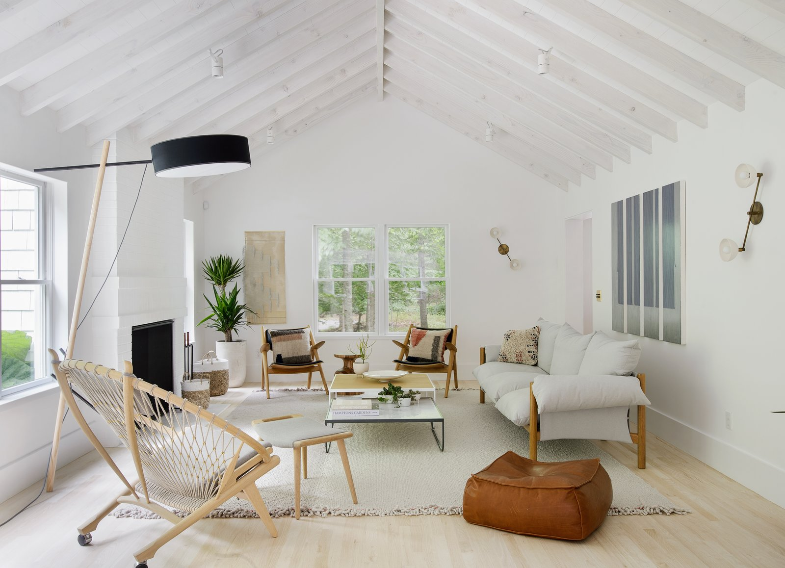 Living Room, Ceiling Lighting, Standard Layout Fireplace, Wall Lighting, Floor Lighting, Chair, Lamps, Ottomans, Rug Floor, Sofa, and Light Hardwood Floor Taking cues from their style-conscious clients, Jessica Helgerson Interior Design transformed an Amagansett home into a light-filled, Scandinavian-inspired getaway.  Photo 1 of 5 in How Much Should You Spend on a Living Room Sofa? from A Hamptons Beach Retreat Gets a Scandinavian-Style Makeover