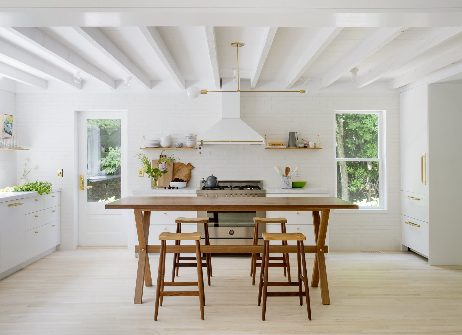 Kitchen, Range Hood, Range, Wall Oven, Marble Counter, Pendant Lighting, Subway Tile Backsplashe, Ceiling Lighting, White Cabinet, and Light Hardwood Floor Taking cues from their style-conscious clients, Portland-based Jessica Helgerson Interior Design transforms an Amagansett home into a light-filled, Scandinavian-inspired getaway. The kitchen expanded to a location where there had been a screened-in porch, increasing its interior footprint.  Best Photos from A Hamptons Beach Retreat Gets a Scandinavian-Style Makeover