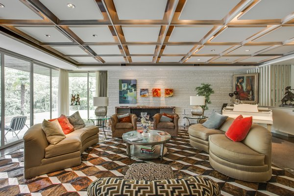 The living room area features recessed lighting and terrazzo flooring with brass filings.